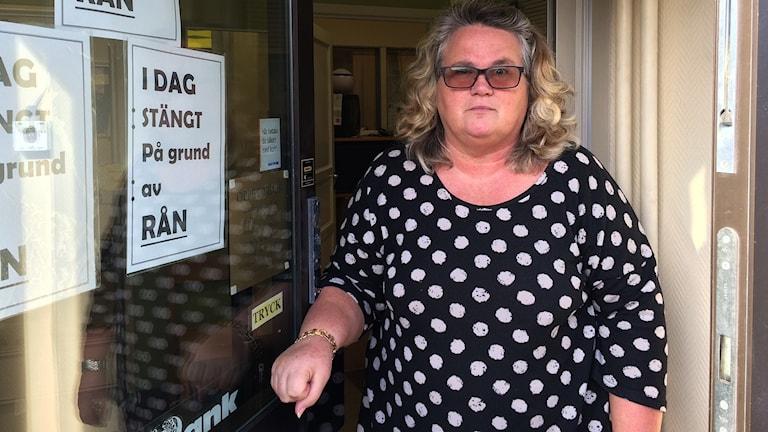 """Lapp med texten """"Idag stängt på grund av rån"""" på dörren. Birgit Kalm Sahlin som jobbar i pantbanken står i dörren. Foto: Ingrid Engstedt Edfast/Sveriges Radio"""