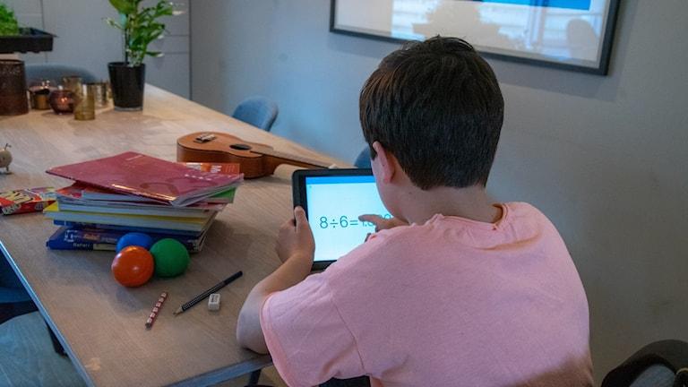 Ett barn sitter med ryggen till vid ett bord och håller i en läsplatta, på bordet finns en hög med skolböcker.