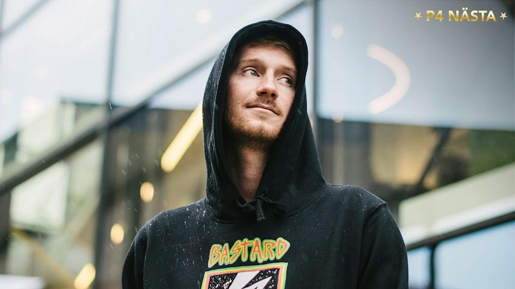 Porträtt på Joakim Gissberg med uppdragen svart huva. I bakgrunden en fasad i glas som återspeglar stadsbelysningen. Foto: Petra Berggren/Sveriges Radio
