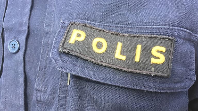 """Närbild på Polismärke med texten """"Polis"""". Foto: Alexander Arvidsson/Sveriges Radio"""