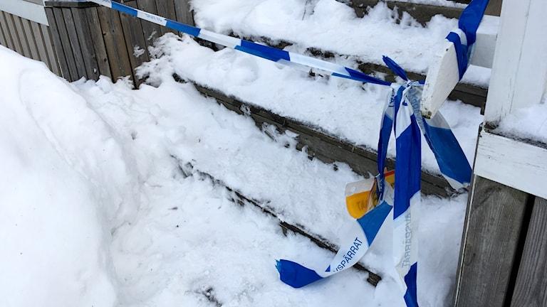 Polisens platsband spärrar av en oskottad trätrappa upp till bostaden där kvinnan misshandlades. Foto: Anton Kårén/Sveriges Radio