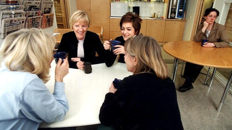 Fyra glada kvinnor samtalar vid ett fikabord. Bakom vid ett annat bord sitter en ensam ledsen kvinna.