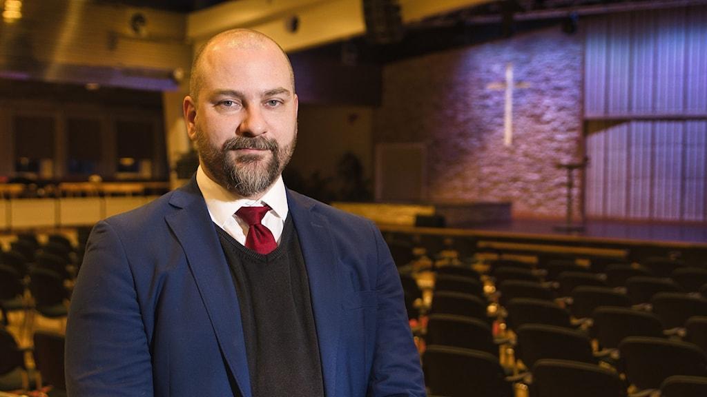 Pastor Christian Mölk står inne i kyrksalen i Pingstkyrkan i Härnösand. Foto: SVT