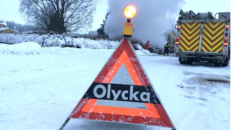 Varningstriangel med texten olycka utställd på en snötäckt väg