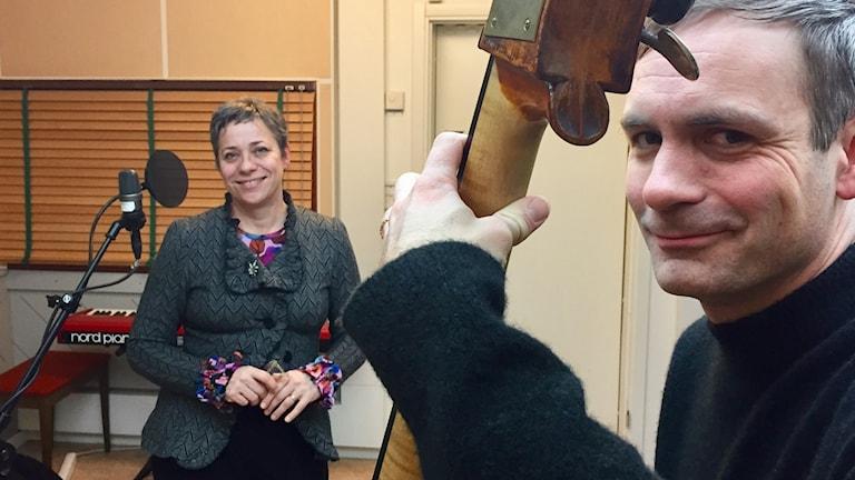Lina Nyberg och Josef Kallerdahl står i P4 Västernorrlands studio. Josef tar ett ackord på sin kontrabas. Foto: Karin Lönnå/Sveriges Radio