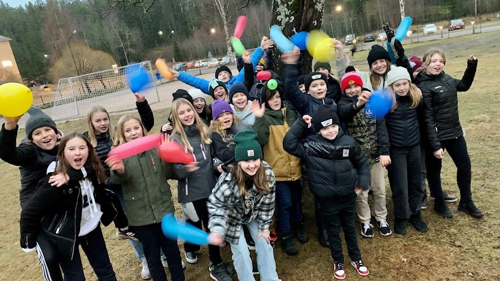 En femteklass står framför ett träd och jublar och viftar med ballonger. Foto: Karin Lönnå/Sveriges Radio