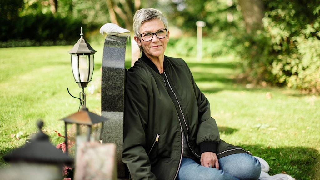 Jane Rönnqvist sitter lutad mot baksidan av dottern Nathalies gravsten. Foto: Petra Berggren/Sveriges Radio