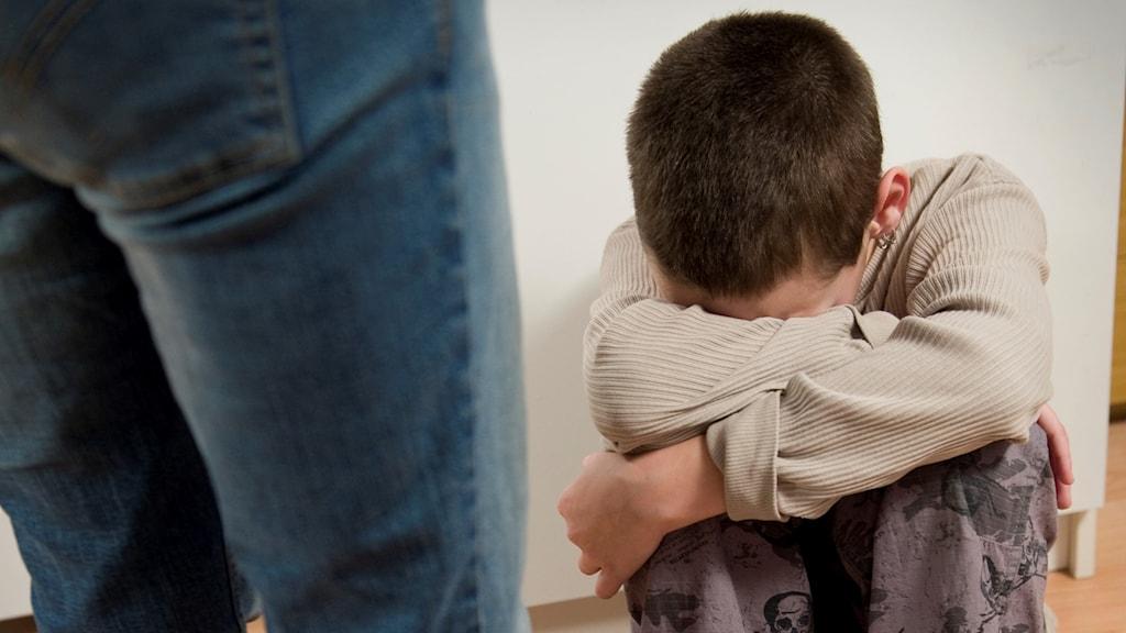 Pojke sitter med ansiktet dolt och verkar ledsen. Vuxens ben hotfullt i förgrunden.