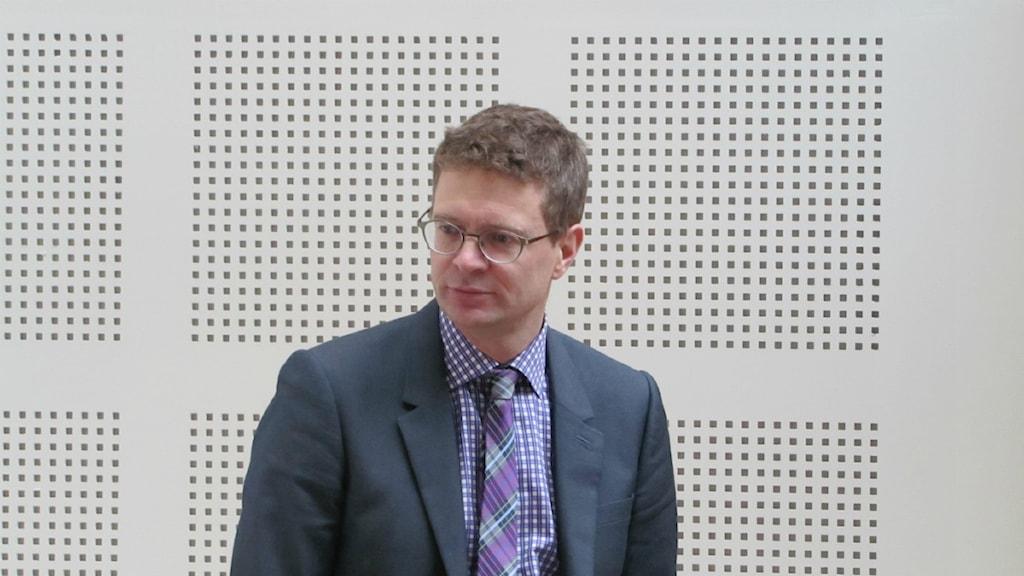Åklagare Daniel Brodén står mot en vägg och tittar snett neråt