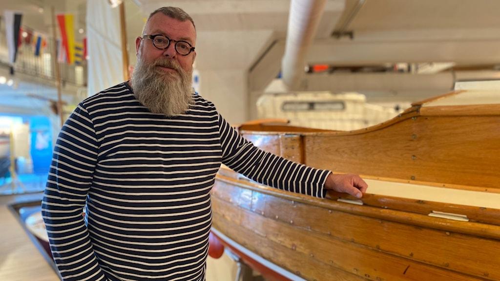 Man med skägg och randig tröja vid en båt
