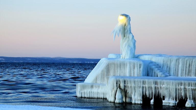En helt isbelagd kaj med trappa och lyktstolpe. Foto: Britt Nordberg