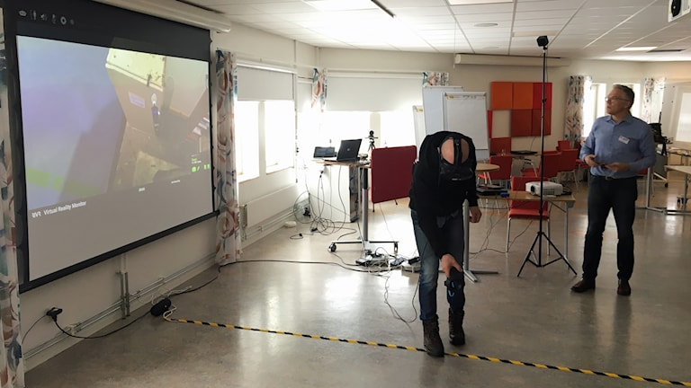 En person testar VR-glasögon vid en storskärm