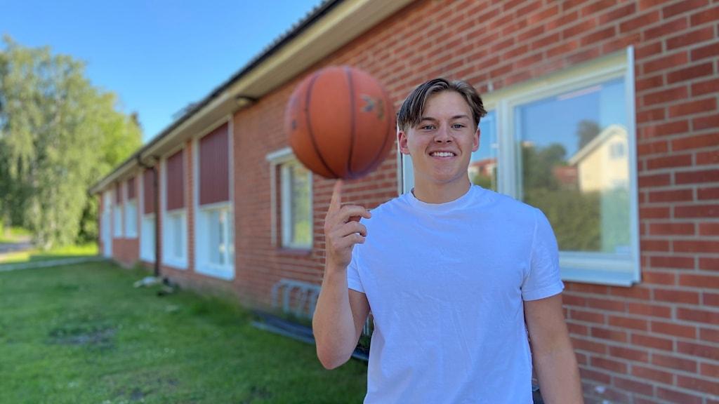 Isac Åhnstrand står med en basketboll och balanserar den på fingret.
