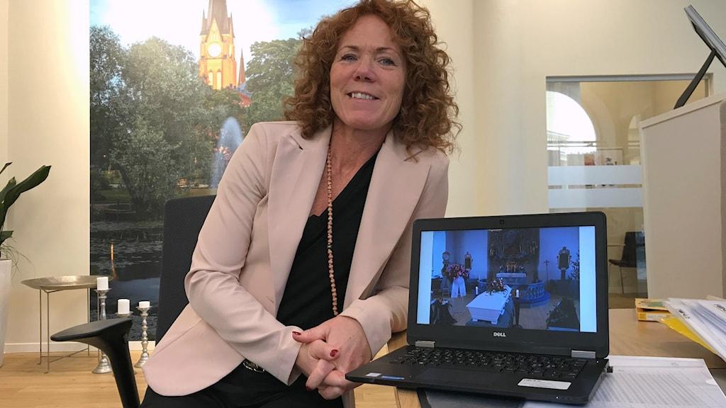 Pia Alm, Fonus i Sundsvall, framför en dataskärm som visar en bild från en begravning.