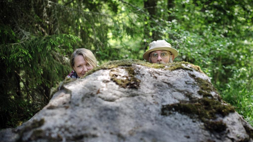 Ulla och Fredrik gömmer sig bakom en sten