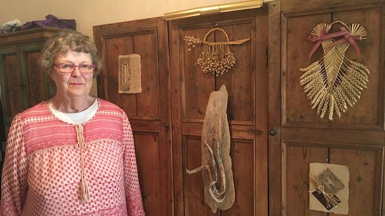 Gun-Marie Jangdahl i Kramfors framför en vägg hon skapat av återvunna dörrar till en skänk.