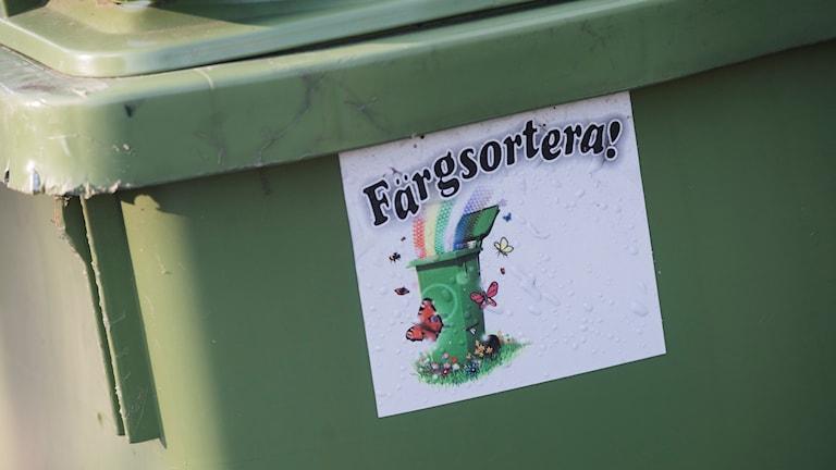 """En grön soptunna med ett klistermärke där det står """"Färgsortera!"""" Foto: Fredrik Sandberg/TT"""