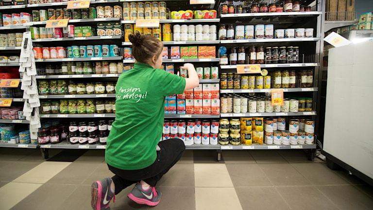 Ung kvinna ställer upp varor på hylla i en matbutik. Foto: Fredrik Sandberg/TT