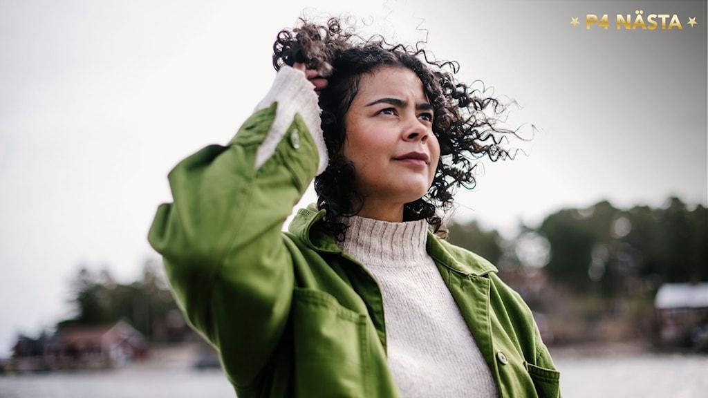 Isabel Neib står vid havet och vinden blåser i hennes hår. Hon håller undan lite av håret för att det inte ska täcka ansiktet. Foto: Petra Berggren/Sveriges Radio