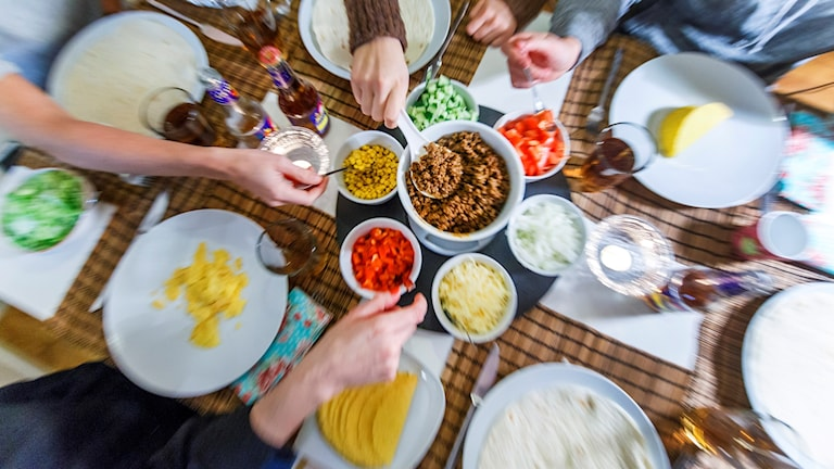 Ett matbord dukat med olika taco-ingredienser och händer som öser ur skålar och kärl.