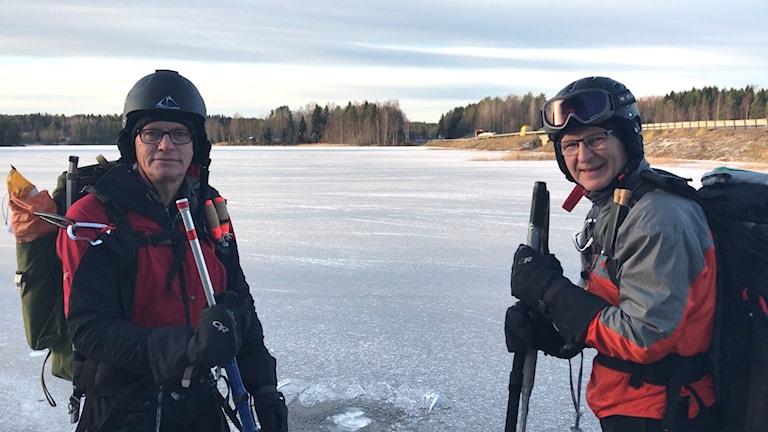 På isbelagd Bölesjön står Roger Bergström och Per Mickelsson i utrustning för att åka långfärdsskridskor, inklusive hjälm. Foto: Fredrik Birging/Sveriges Radio