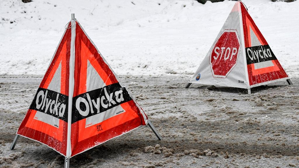 Räddningstjänsten varnar med skyltar om en olycka på en väg.