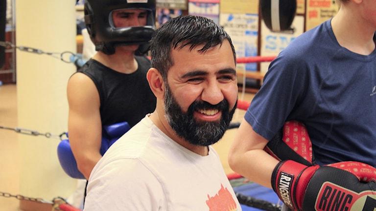 En leende och skäggprydd Erfan Kakahani omgiven av boxare i lokalen.