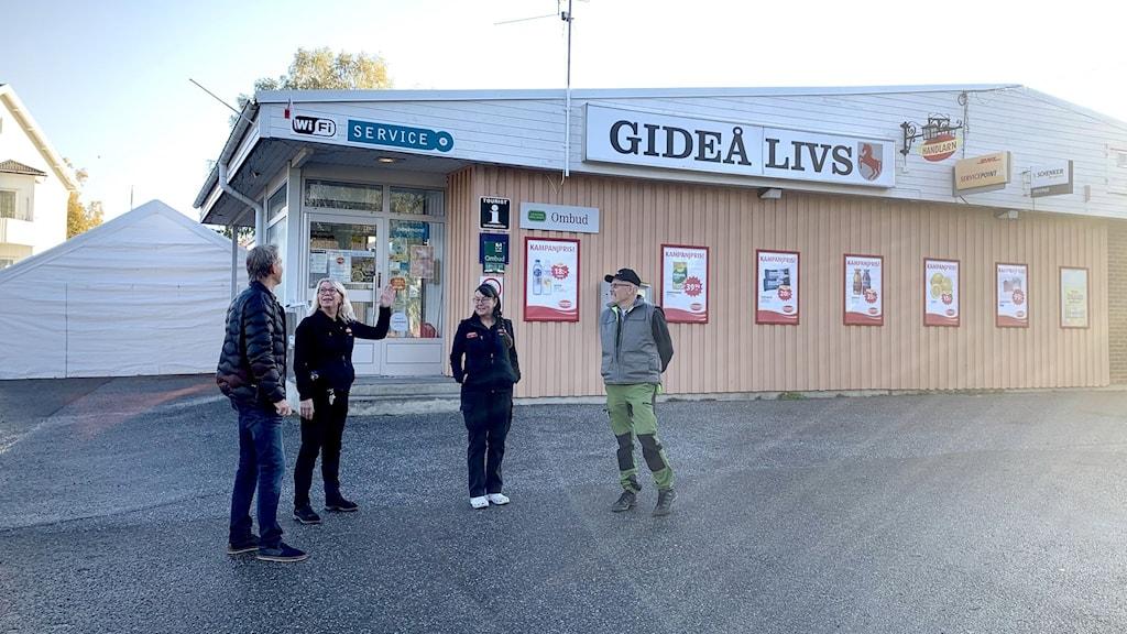 Fyra personer står på parkeringen framför en mindre matbutik.