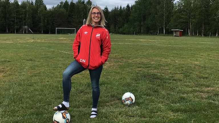kvinna som står vid en fotboll
