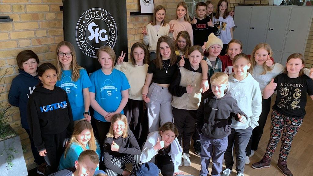 Klass Vintergatan på Sidsjö Fristående Grundskola, SFG, är glada och gör segertecknet när de står uppställda i en korridor på skolan. Foto: Linda Rahm
