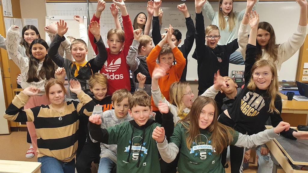 Klass 5A på Sundskolan i Örnsköldsvik står tillsammans, jublar och räcker upp händerna för att de vunnit den första kvartsfinalen i Vi i femman. Martin Gustavsson och Lova Persson i laget istter längst fram i sina gröna Vi i femman-tröjor. Foto: Elin Telhammer