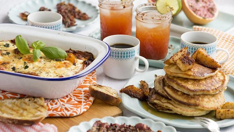 Uppdukat för brunch med portugisiska ägg, amerikanska pannkakor och rosépepparbacon.