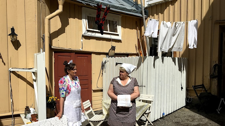 Två kvinnor står på innergård med mamelucker på tork på klädstreck. Foto: Ulla Öhman/Sveriges Radio