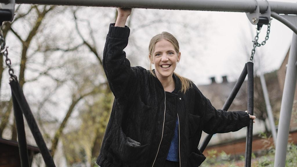 Anna Westin står i svart jacka vid en gungställning utomhus. Foto: Petra Berggren/Sveriges Radio