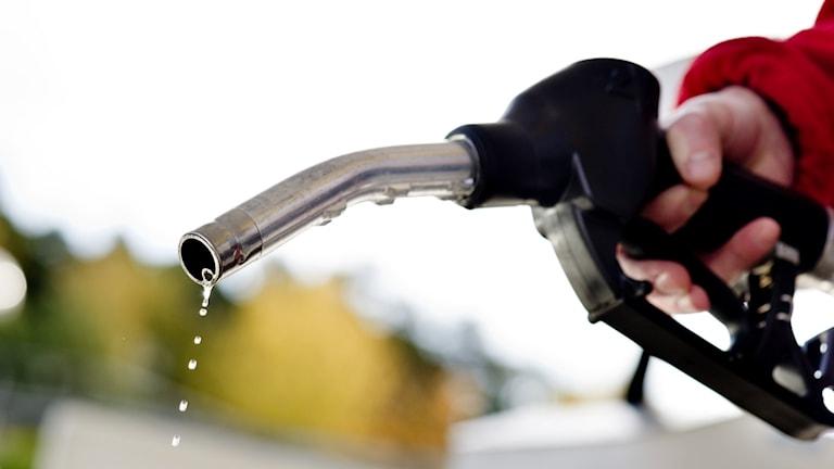 Ett tankhandtag som det rinner bensin ur.