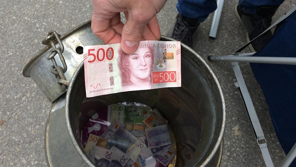 En 500-sedel ska precis släppas ner i insamlingskrukan som redan har många sedlar på botten. Foto: Lennart Sundwall/Sveriges Radio