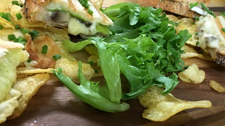 Delade varma mackor och chips på en ekbräda tillsammans med en stor skål basilkapesto. Foto: Ann-Charlotte Carlsson/Sveriges Radio