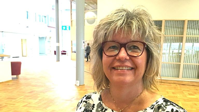 Ingrid Nilsson med fluffigt hår och glasögon med mörkröda bågar.
