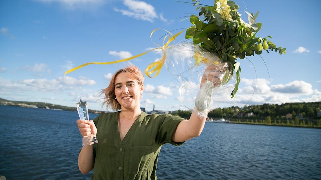 Artisten Nina Bring står på kajkanten i Örnsköldsvik, håller upp en stor blombukett mot himlen.