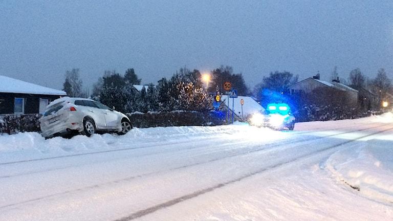 Bil fastnat i snödriva i Sundsvall efter att ha kört av vägen. Polis på plats. Foto: Christer Jonasson/Sveriges Radio