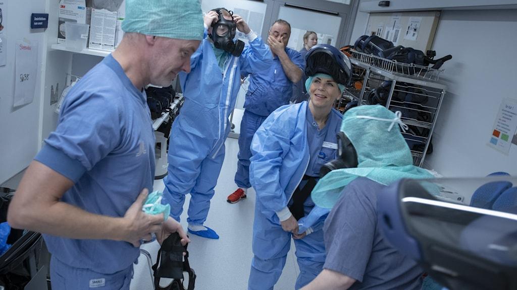Vårdpersonal som vårdar covid-19 sjuka avlöser varandra i en sluss.