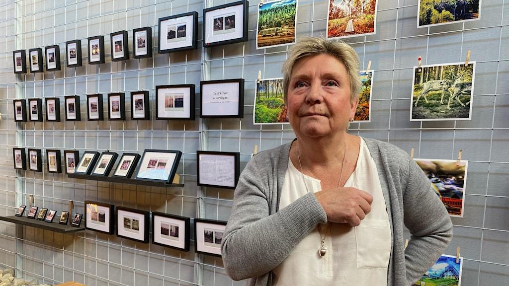 En kvinna i grå pullover står framför en grå vägg med massa tavlor på.