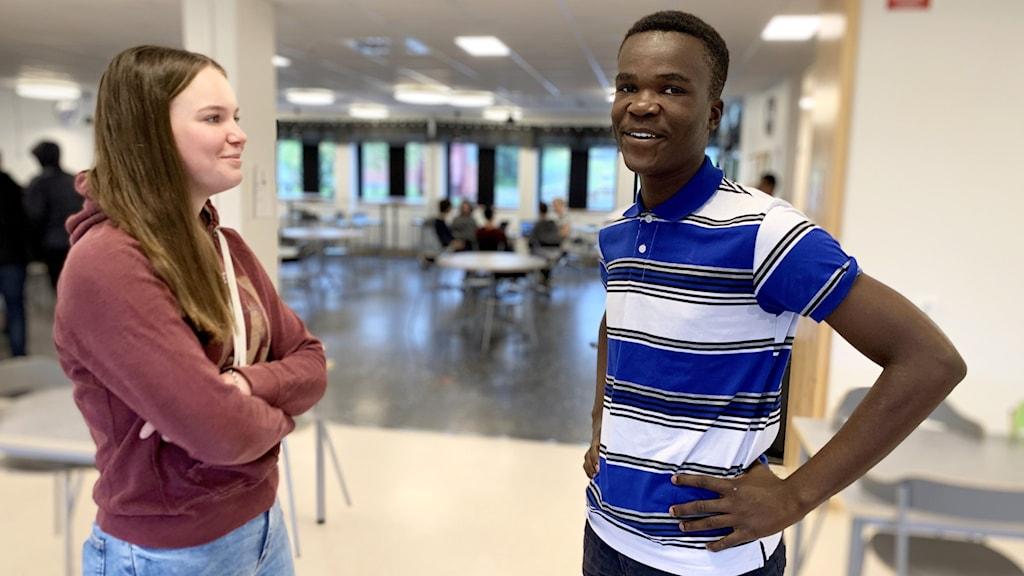 Två elever står i en skolmatsal. Tjej till vänster kille till höger.