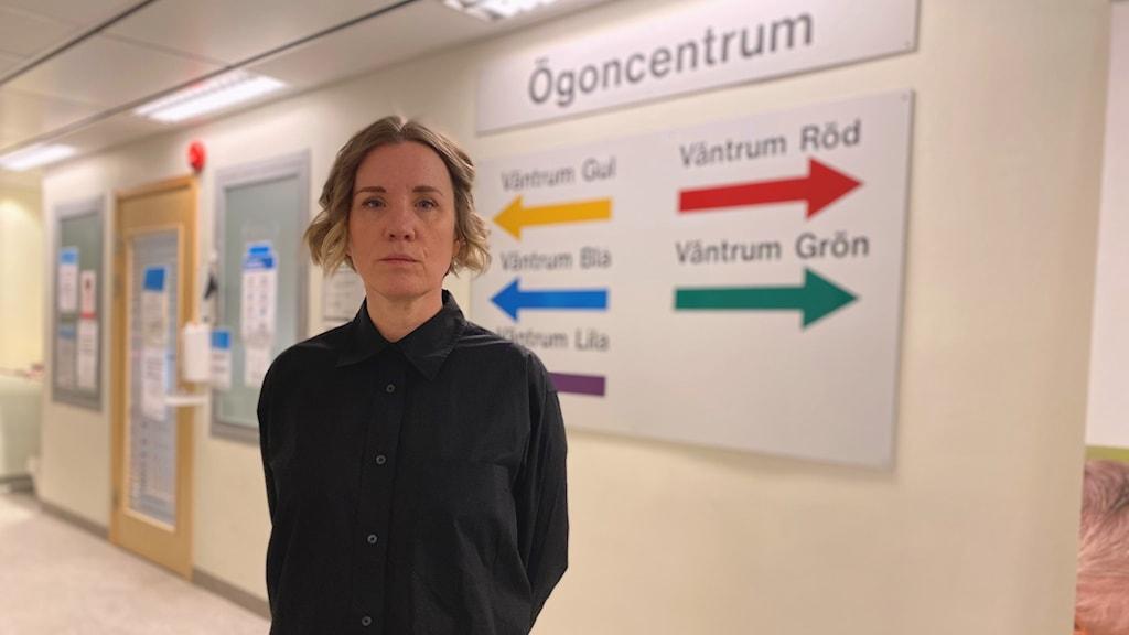 Kvinnlig chef framför skylten till ögoncentrum i sjukhuskorridor.