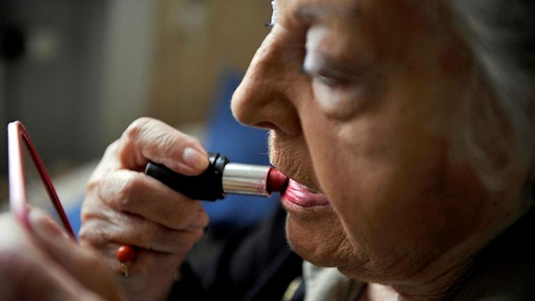 Äldre kvinna målar läpparna med hjälp av en fickspegel. Foto: Bertil Ericson/TT