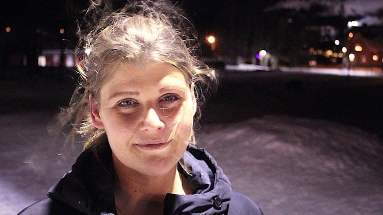 Camilla Löfdahl står i ljuset av en gatlykta en mörk vinterkväll. Foto: Peter Hansson/Sveriges Radio