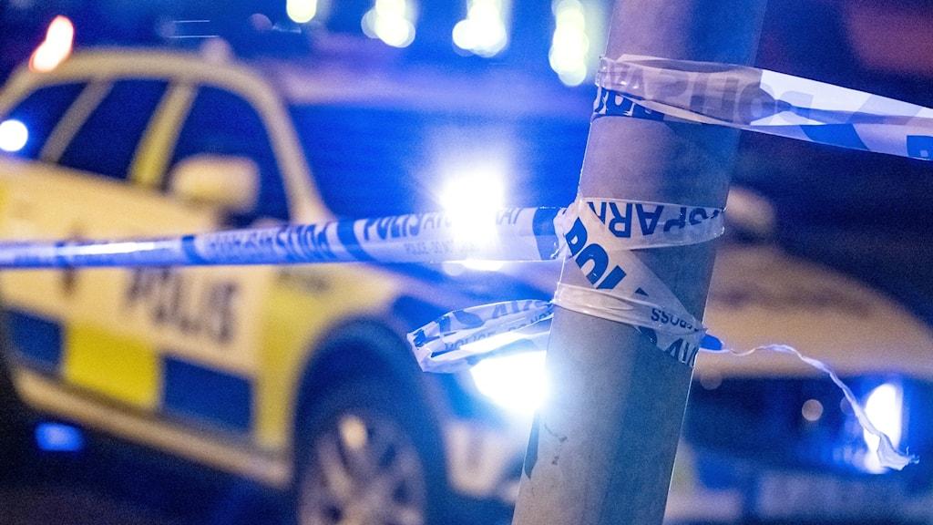 Polisbil med avspärrningsband, som blinkar i natten.