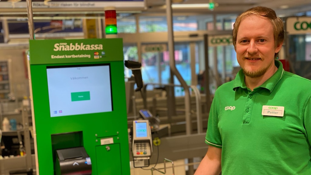 Petter Walker är butikschef på livsmedelsbutiken Coop i Ånge. Han har på sig en grön, kortärmad skjorta med företagets logotyp trycke på bröstet. Han står intill snabbkassan som förkunnar att här går det inte att betala med kontanter.