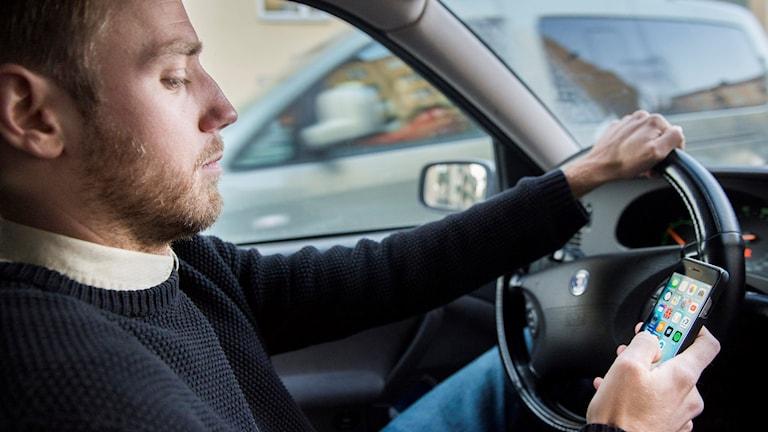 En man kör bil och använder samtidigt sin mobil. Foto: Erik Nylander/TT