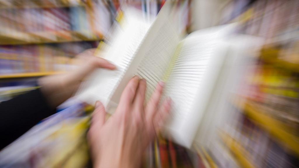 En person bläddrar i en bok.